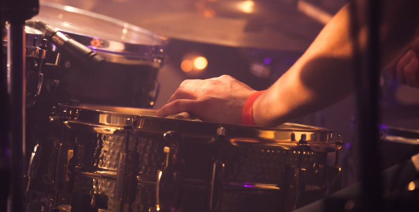 Vintage warm toned live music background, drummer plays with drumsticks on rock drum set. Closeup photo with soft selective focus