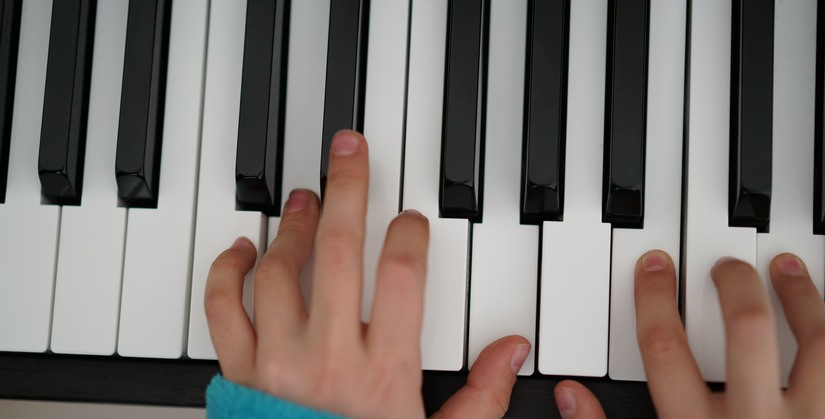 Childrens hands on piano keys
